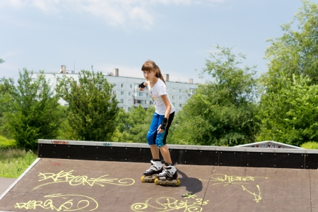 poised: Beautiful young teenage female roller skater poised on the top of a cement ramp covered in yellow graffiti about to start her descent