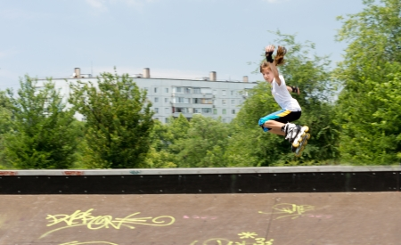 rollerskater: Young teenage girl jumping high in the air from the top of a cement ramp on her blades as she practises her aerobatics