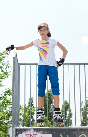 rollerskater: Young attractive teenage female roller skater posing at the top of a cement ramp in her  blades looking down at the camera with her hand on her hip