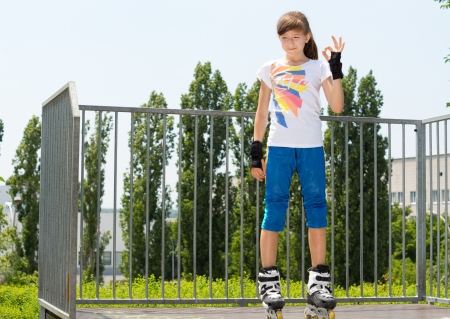 rollerskater: Smiling young girl giving a Perfect gesture as she stands at the top of a cement ramp at a skate park in her skates Stock Photo
