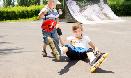 rollerskater: Young girl falling while roller skating in a skate park landing on her bottom with her arms and legs flying Stock Photo