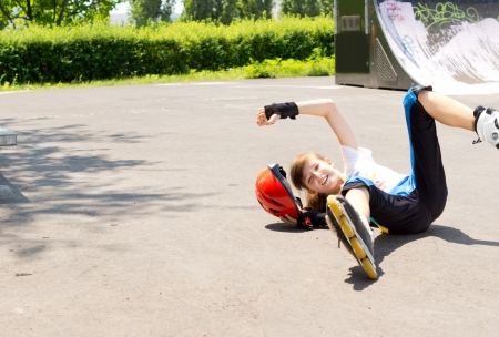 rollerskater: Young girl has an accident while roller skating losing her balance and landing on her back with her limbs flying with copyspace