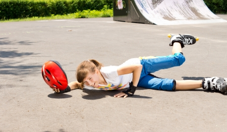 sprawled: Chica joven que cae mientras que el patinaje sobre ruedas mentira tendido en el asfalto con el casco en la mano y la pierna en el aire