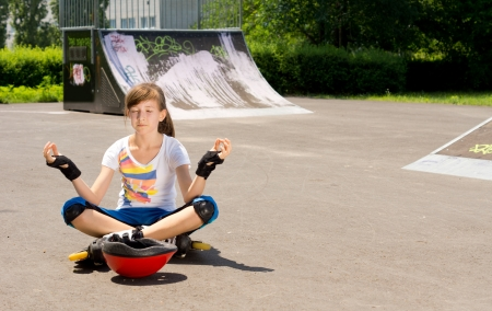 rollerskater: Pretty young teenage girl in  blades sitting meditating on the tarmac at a skate park sitting n the lotus position with her eyes closed Stock Photo