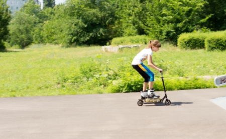 Young girl riding a scooter in the park in her rollerblades balancing on the foot board with difficulty with copyspace photo