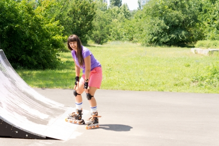 poised: Young girl roller skating poised at the bottom of a cement ramp at a rural skate park smiling at the camera