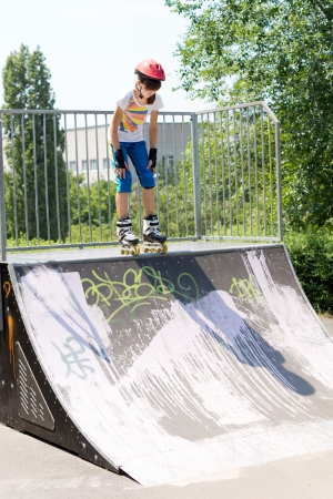poised: Teenage girl on a roller skating ramp poised at the top as she prepares to launch herself downwards to perform aerobatics Stock Photo