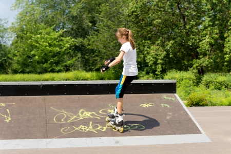 facing away: Young slender teenage girl roller skating in the park riding up a shallow cement ramp with graffiti facing away from the camera