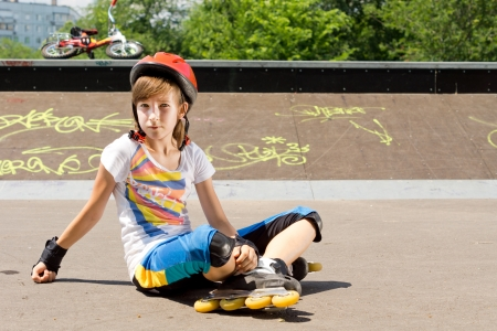 rollerskater: Young girl in skate  sitting on the tarmac in the sun wearing a safety helmet watching something out of frame