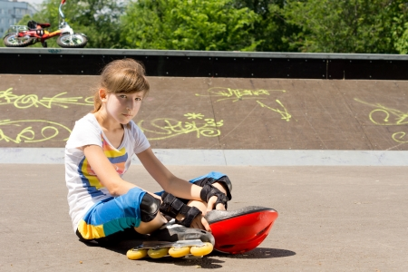 rollerskater: Young girl wearing skate relaxing at the skate park sitting in the sun on the asphalt with her helmet resting on the ground in front of her Stock Photo