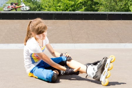 sustained: Young female teenage roller skater sitting on the tarmac rubbing her calf muscle to relieve a cramp or muscle strain sustained enjoying the sport