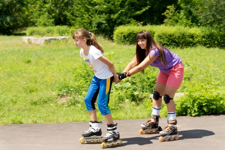 roller skating: Two attractive teenaged female friends roller skating with the one pulling the other along behind her in a lush green rural park Stock Photo