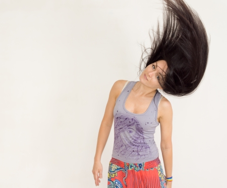 Beautiful trendy young woman tossing her long straight brunette hair high into the air standing in front of a neutral background with copyspace