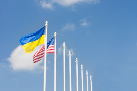 flagpoles: Flags of the Ukraine and United States of America flying in the breeze from a line of metal flagpoles against a clear blue sky with copyspace