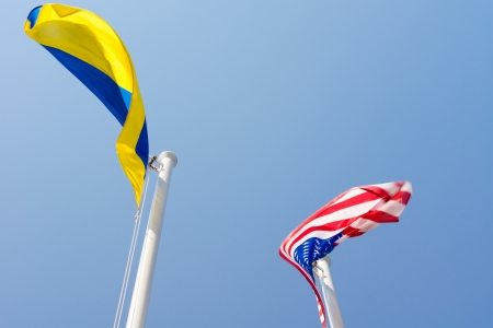 flagpoles: American and Ukrainian national flags flying from the top of metal flagpoles against a clear blue sky Stock Photo