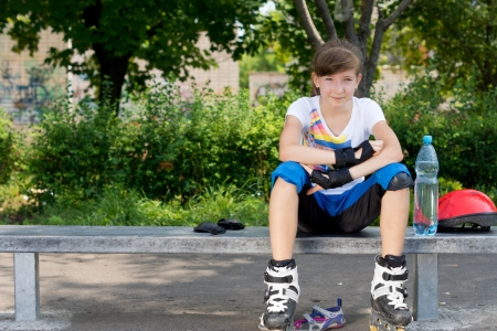 rollerskater: Young woman on roller skates sitting on the bench with bottled water Stock Photo