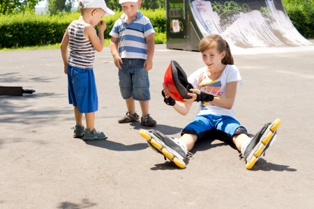 Woman on roller skates holding her hat in the park photo
