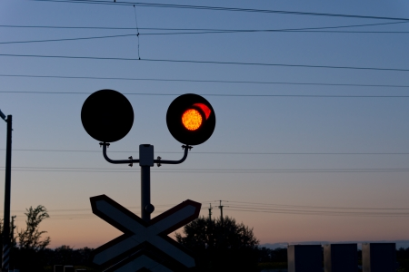 Railroad red traffic signal at a level crossing or grade crossing warning cars of an approaching train at dusk photo