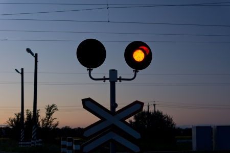 Red signal at a railway crossing above a traffic sign as a warning to cars to stop and not cross the lines as there is an approaching train photo