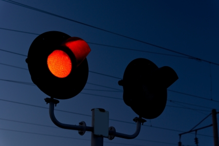 Closeup of a red signal light at a level crossing or grade crossing warning motorists of an approaching train and halting traffic photo