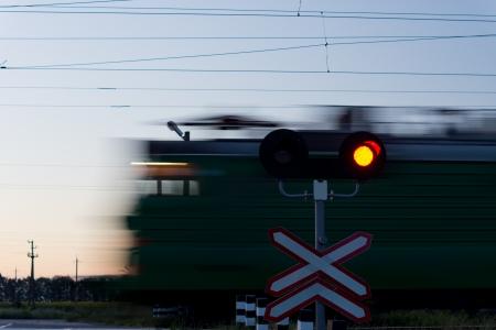El exceso de velocidad del tren que pasa un paso a nivel con una se�al roja en primer plano para evitar que los coches que cruzan la l�nea de