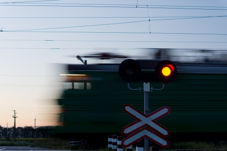 Speeding train passing a level crossing with a red signal in the foreground to prevent cars crossing the line Stock Photo