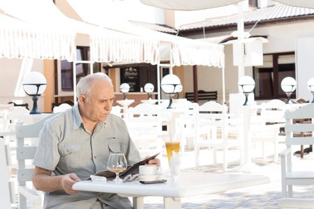 Elderly man checking his bill at an outdoor cafe after enjoying drinks and refreshments Stock Photo