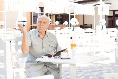 summoning: Elderly man summoning a waiter to take his order while sitting at a table at an open-air cafe Stock Photo