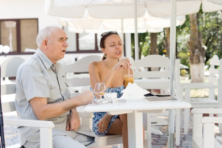 Two friends, an elderly man and attractive stylish young woman, sitting chatting at a table at an outdoor cafe photo