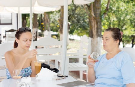 Mother and daughter having drinks sitting together at a table at an outdoor restaurant on a hot summer day photo