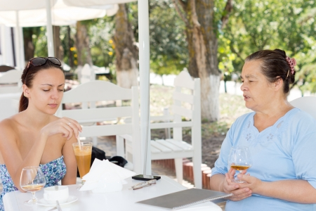 Mother and daughter having lunch together sitting enjoying their drinks at an outdoor restaurant before ordering their food photo