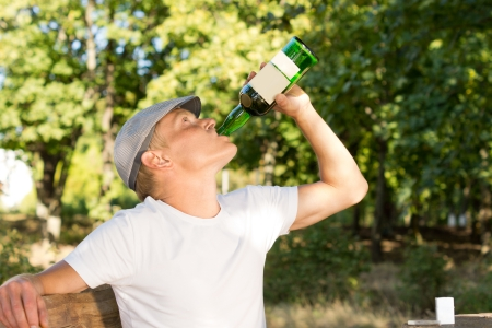 addictive drinking: Alcohol male abuser drinking from a bottle of white wine sitting on a bench in the park in a warm summer day