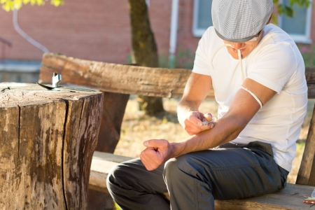 Addicted man sitting on a bench outdoors injecting his left arm intravenously photo