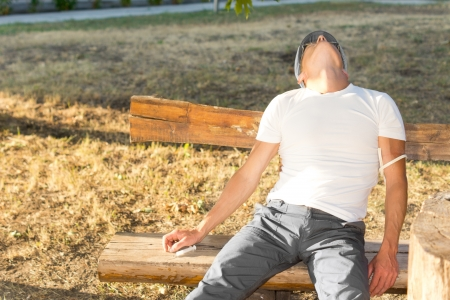 euphoria: Middle-aged man experiencing euphoria after using psychoactive drugs sitting on a bench in the park