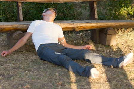 Heroin user lying down leaning on a bench in the park experiencing a state of relaxation and euphoria photo