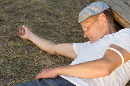 intravenously: Heroin user experiencing unconsciousness after drug dose administered intravenously Stock Photo
