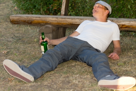 Passed out: Drunk Caucasian adult man lying down on the ground experiencing euphoria after excessive drinking