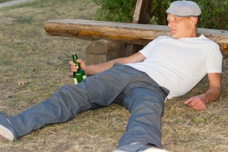 incapacitated: Drunk man fallen down on the ground with a bottle in his hand leaning his head on a bench in the park Stock Photo