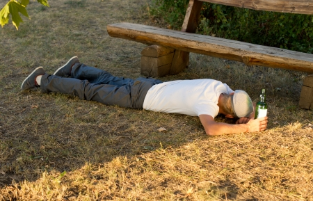 addictive drinking: Jobless man sleeping on the ground outdoors next to a bench after excessive drinking