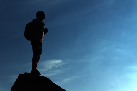 Silhouette of a lonely male hiker standing on the mountain top in the evening Stock Photo