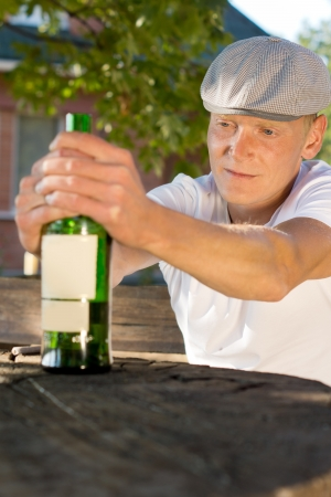 boozer: Drunk depressed middle-aged man holding a bottle of wine sitting at a wooden table outdoors