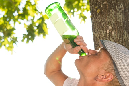 Close-up horizontal profile portrait of an addict drinking from a bottle of white wine outdoors