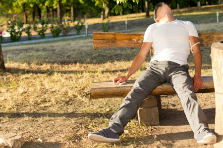 drug use: Addict man experiencing side effects of injectable drug use, in the park Stock Photo