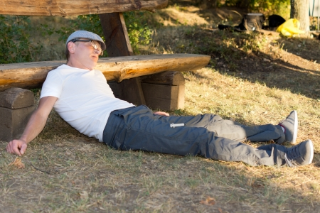 Heroin user passed out on the ground with his head on a bench in the park photo