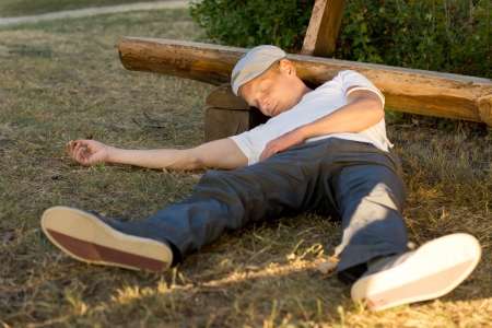 passed out: Heroin abuser passed out in the park after an overdose in summer Stock Photo