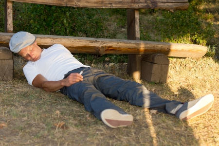 passed out: Addicted man passed out on the ground in the park because of an overdose Stock Photo