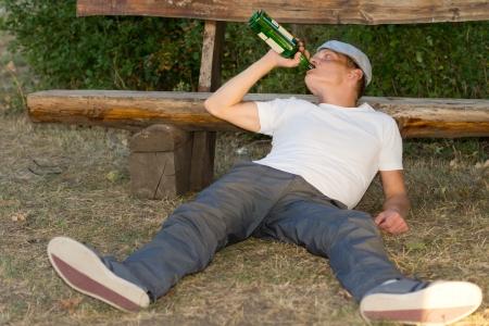 Desempleado hombre adulto sentado en el suelo bebiendo de una botella de bebida alcoh�lica Foto de archivo