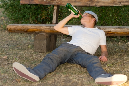 Jobless adult man sitting on the ground drinking from a bottle of alcoholic beverage
