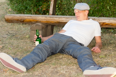 addictive drinking: Addicted man lying on the ground experiencing lethargy after excessive drinking