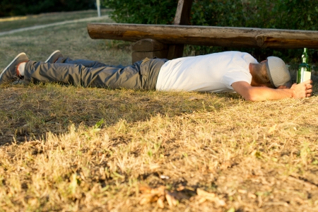 incapacitated: Drunk man sleeping on the ground next to a bench with a hand on a bottle of white wine